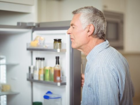 Senior man looking in refrigerator